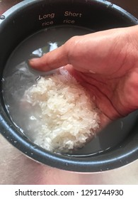 Hand washing white raw grains of rice in cooker pot.