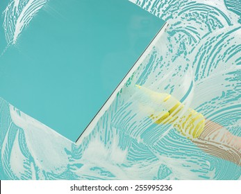 hand washing window with squeegee revealing clear blue sky