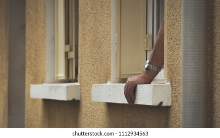 Hand with watch leaning on window in france