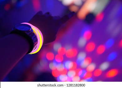 Hand with a watch and pink and yellow neon bracelets in the air during a neon party with blurry lights in the background