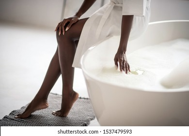 Hand in water. Close up of dark-skinned young woman putting hand in water in bath with foam