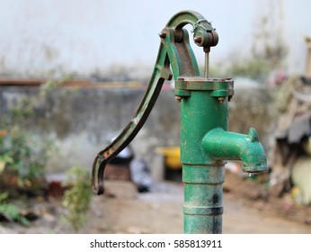 Hand water pump with a water drop in an Indian village