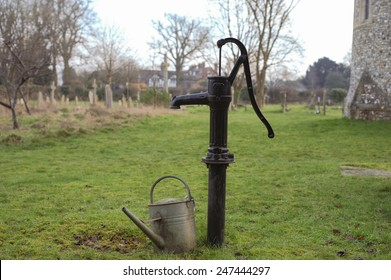 Hand Water Pump and Watering Can in the Churchyard of the Berkshire Village of Whitchurch Hill, England, UK