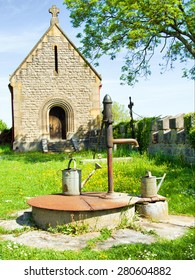 Hand Water Pump and Watering Can in the Churchyard