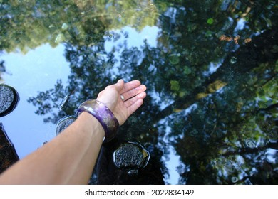 Hand in water. Scenic view of the neon blue waters of a karst spring, spring (outflow of groundwater) that is part of a karst hydrological system. Blue Springs in Tomaszow Mazowiecki, Poland, Europe