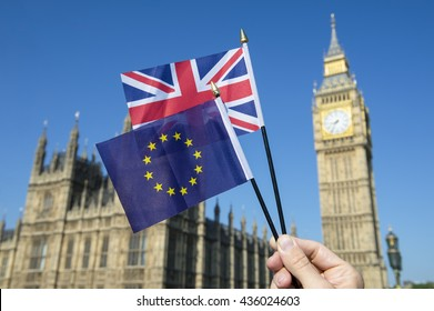 Hand waving European Union and British Union Jack flag in front of Big Ben and the Houses of Parliament at Westminster Palace, London as the Brexit process moves ahead