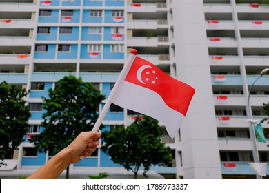 Hand waving Singapore flag outside on sunny day, against background of HDB flats and trees foliage. Many residents hang Singapore flags over balconies.
