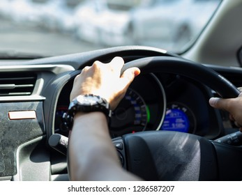 Hand wear clock driving a car by steering wheel of car in blurry background , image using for interior car and drivers