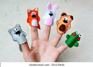 Hand wearing 5 finger puppets; wolf, fox, rabbit, bear, frog