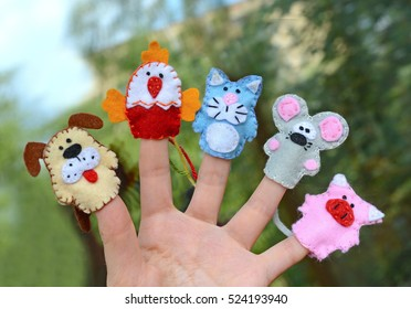 Hand wearing 5 finger puppets: dog, cock, cat, mouse, pig