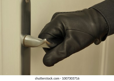 Hand wearing black leather glove on door handle. Stealing. Industrial espionage.