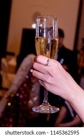 A hand wearing a diamond ring holding a glass of Champagne