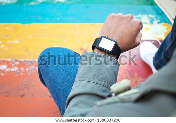 Hand wearing elegant smartwatch with blank screen.