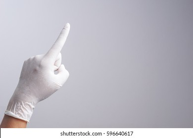 Hand wearing latex glove with number one index finger on white background