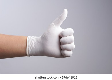 Hand wearing latex glove with thumb up gesture on white background