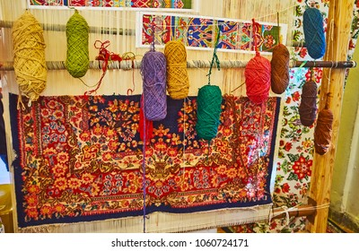 Hand weaving loom with examples of colored woolen yarns  and traditional Persian carpet, covered with fine floral pattern, Mahan, Iran.