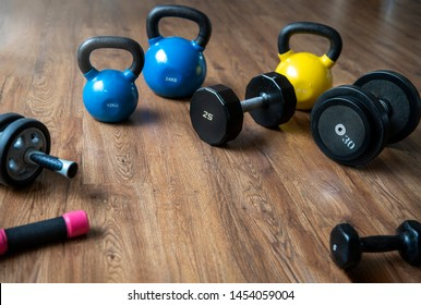 Hand weights Fitness exercise equipment dumbbell, Ab roller and kettlebells weights on wood floor in gym background.