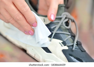 hand with wet wipe clean shoes (sneakers) from dirt and dust