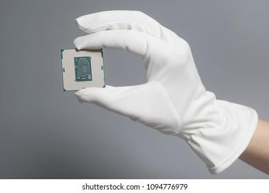 Hand in white glove holding a CPU computer processor microchip.