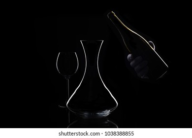 Hand in white glove holds bottle of wine and decanter