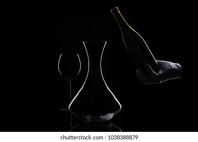 Hand in white glove holds bottle of red wine at bottom and decanter