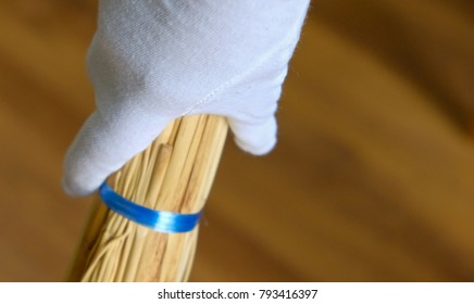 A hand in a white glove holds a broom for Cleaning and sweeping room