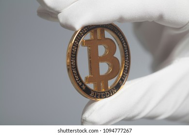 Hand in White Glove holds Golden Bitcoin Crypto Currency .Mining concept.