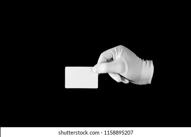 Hand in a white glove on a black background. Credit card. Gesticulation.