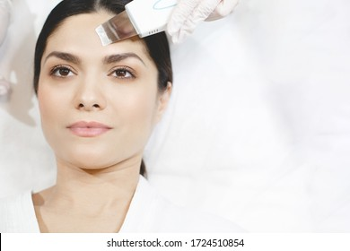 Hand in white glove using peeling toll for facial skin care. Young woman as client lying concentrated calm and peaceful. Beauty routine in cosmetologist's room
