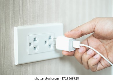 hand and white plug in electric socket on wall.