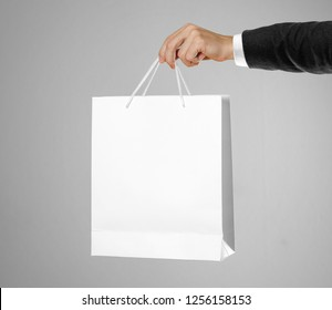 Hand in white shirt and black jacket holds a white gift bag.