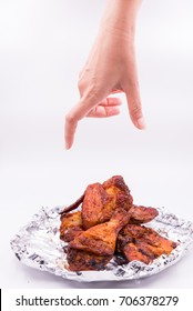 Hand will catch wing, leg delicious grill chicken on foil on white background