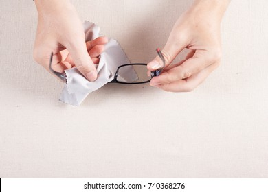 Hand wipe the eyeglass. Man Cleaning the eyeglass with microfiber fabric.