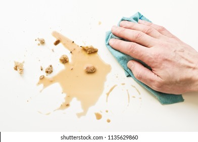 Hand wiping spilled coffee with dish cloth.