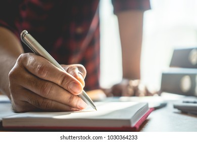 Hand wiritng on to a notebook on office desk