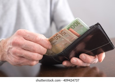 Hand withdrawing money from a wallet