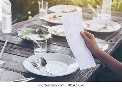 Hand of woman asia Check bill . Pay for food after eating out .