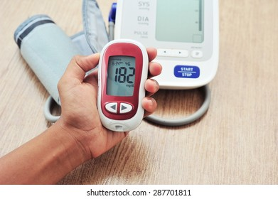 Hand of woman asia holding glucometer. High blood sugar.