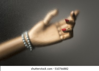 Hand of woman behind a car window. Imitation of a scene from a movie. Isolated on dark background. With copy space text. Studio Shot.