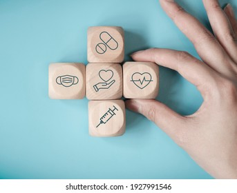 Hand woman choose wood cube stacking with icon healthcare medical on blue background, Health Insurance Concept