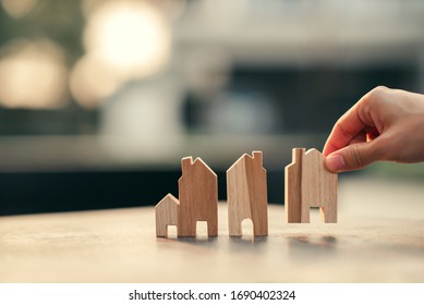 Hand of woman choosing mini wood house model, Planning buy Real Estate, eco house icon concept.