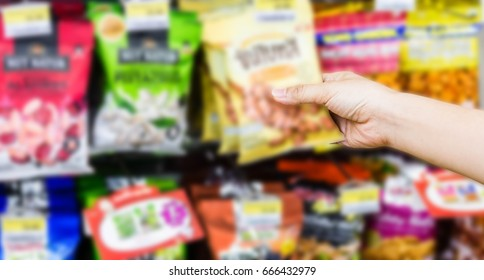 hand of woman choosing or taking sweet products, snacks on shelves in convenience store
