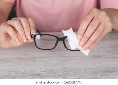 Hand woman cleaning her glasses with cloth, Clean lenses of eyeglasses