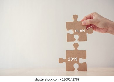 Hand of woman connecting jigsaw puzzle with new year planning 2019