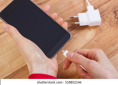 Hand of woman connects plug of charger mobile phone, smartphone charging on table