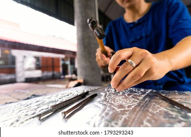Hand of a woman cutting silverware. Thai craftman are making silverware. A craftsman carves intricate drawings into silver or aluminium which is used for silverware.