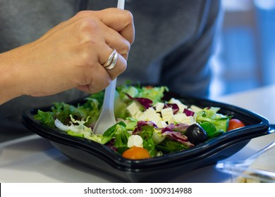 Hand of woman eating fast food salad with plastic fork. Black container to go. Healthy meal on fast food restaurant