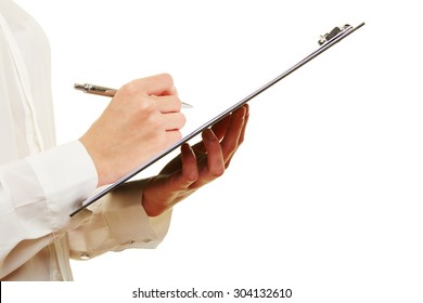 Hand of a woman filling out checklist on a clipboard