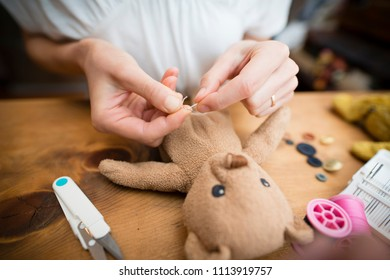 The hand of the woman to fix a stuffed toy