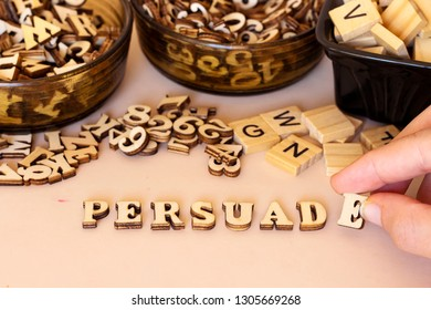 hand woman forming persuade text with small wooden letters and holding letter E